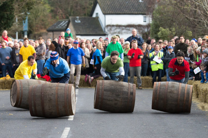 Mandatory Credit: Photo by Geoff Robinson Photography/REX/Shutterstock (5502381d) Competitors trying to control their barrel in the annual Boxing Day Barrel Race in the village of Grantchester near Cambridge. Teams from the four local pubs compete, usually four at a time to roll the empty barrels up the main street as rapidly as possible without injuring the crowds of spectators who risk life and limb while screaming encouragement from behind a thin wall of straw bales. Boxing Day Barrel Race, Grantchester, Britain - 26 Dec 2015